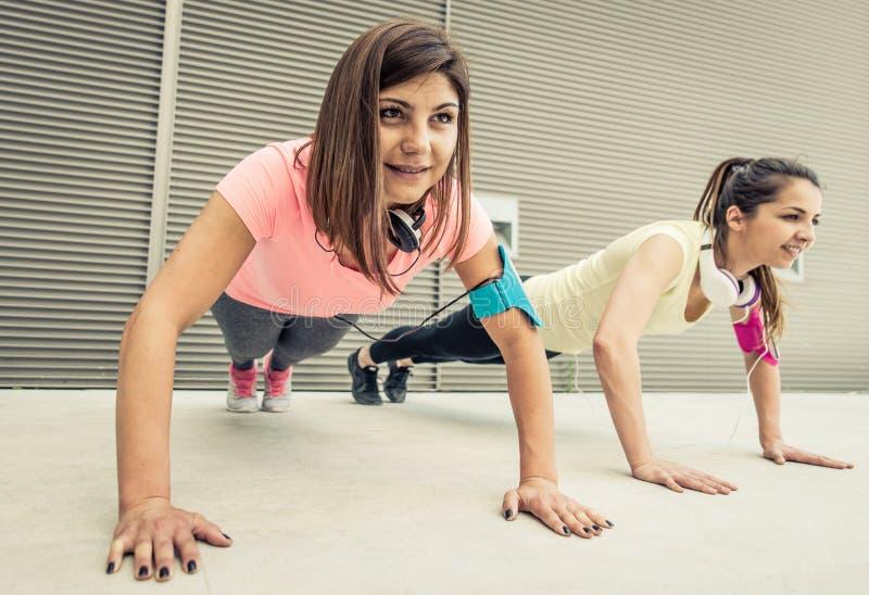Para dziewczyny podnosi szkolenie robić pcha obrazy royalty free