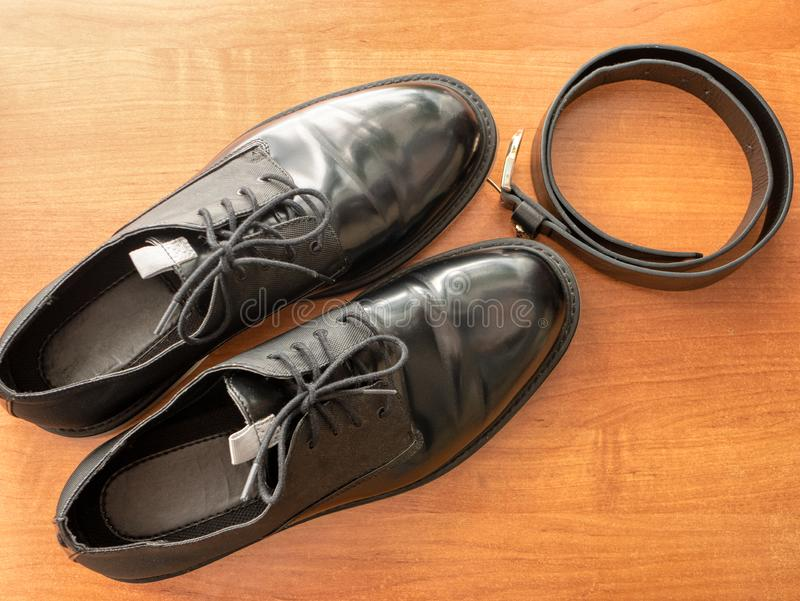 Para eleganccy glansowani czarni formalni mężczyzn buty i rzemienny pasek na drewnianym stole obraz royalty free