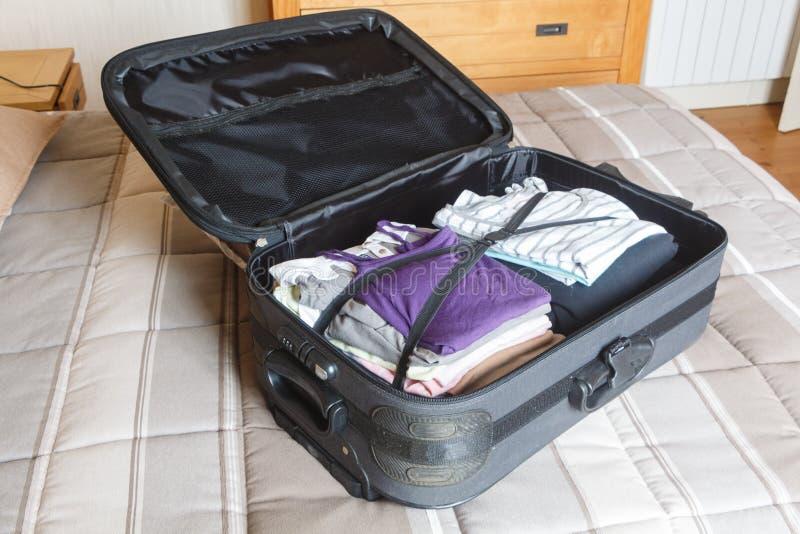 Para embalar a mala de viagem em uma cama fotografia de stock royalty free