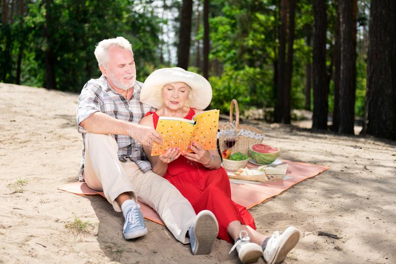 Para emeryt czytelnicza książka podczas gdy siedzący na plaży zdjęcie stock