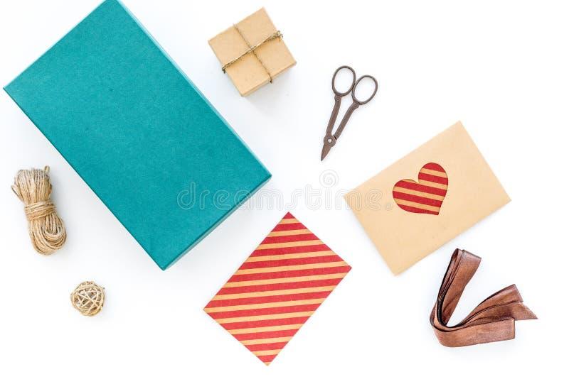 Para envolver o presente Caixa, papel de embalagem, envelope, cabo fino, cartão, fita, sciccors na opinião superior do fundo bran foto de stock