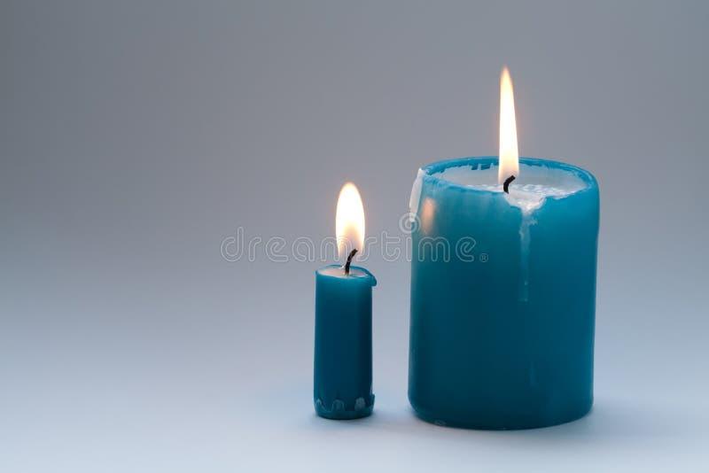 Para färgrika grönaktig-blått, turkosstearinljus på lutninggrå färgbakgrund stycken två varje stearinljus med den naturliga flamm arkivfoton