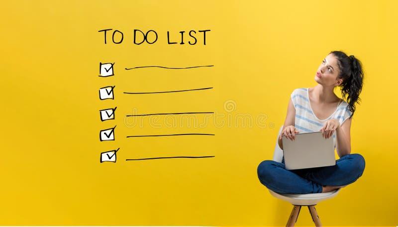Para fazer a lista com a mulher que usa um portátil fotografia de stock royalty free