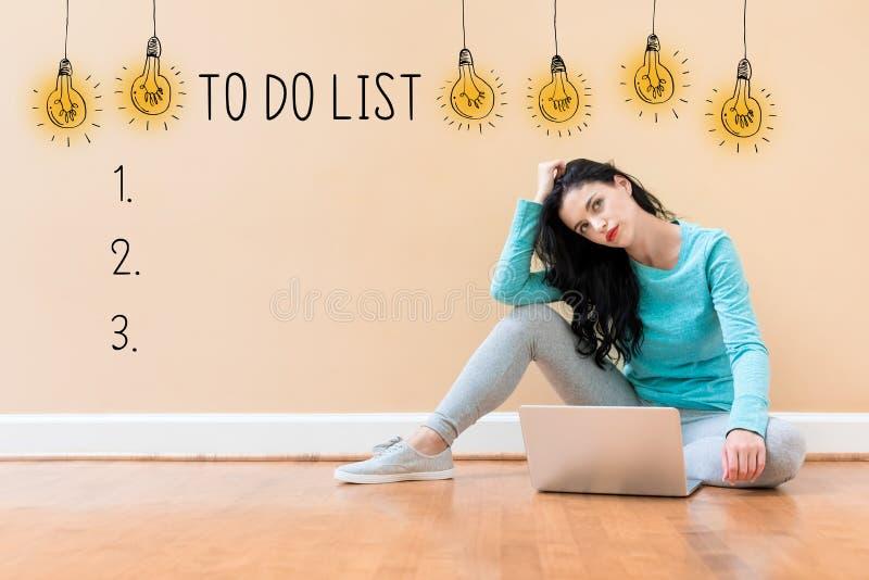 Para fazer a lista com a mulher que usa um portátil fotos de stock