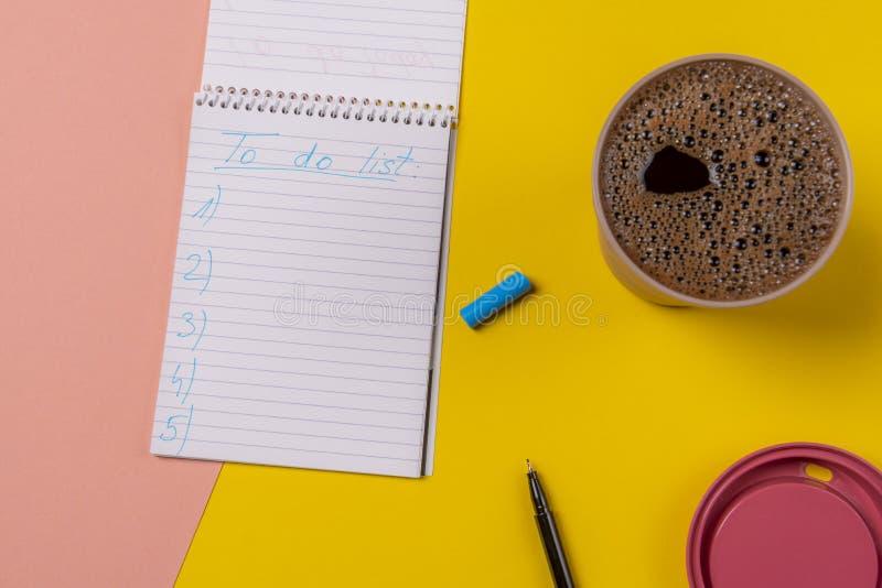 Para fazer lista escrita à mão em um caderno e em um copo do café quente fotografia de stock