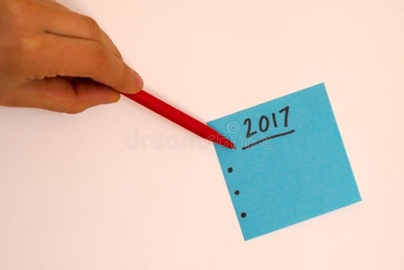 Para fazer a lista pelo ano novo no azul com uma mão e uma pena prontas para escrever foto de stock royalty free