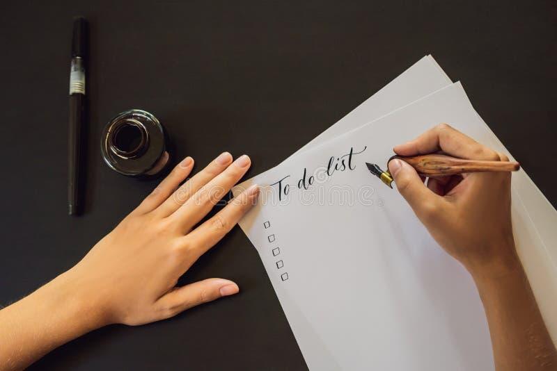 Para fazer o calígrafo Young Woman da lista escreve a frase no Livro Branco Inscreendo letras decoradas decorativas calligraphy imagem de stock royalty free
