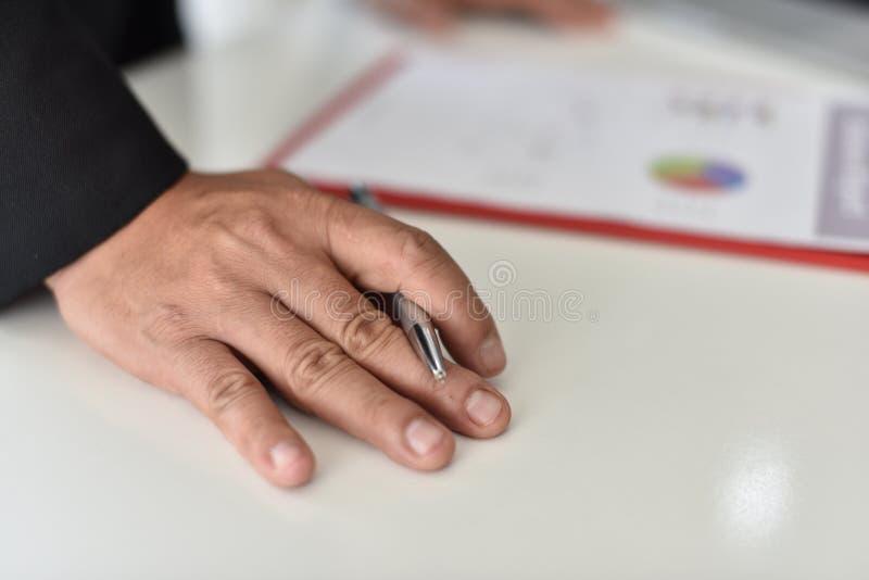 Para firmar, reciba y apruebe Mano del hombre de negocios que señala a la información del gráfico imágenes de archivo libres de regalías