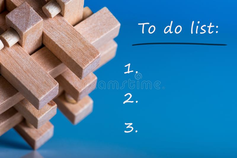 Para hacer la lista en el fondo azul con vista macra del enigma o del rompecabezas de madera imagen de archivo libre de regalías