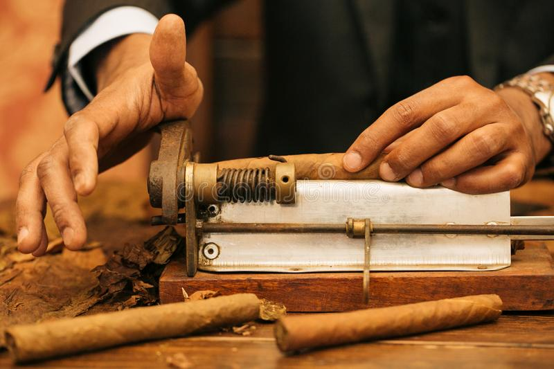Para hacer un cigarro con sus manos, hojas para un cigarro, trabajo hecho a mano imagen de archivo
