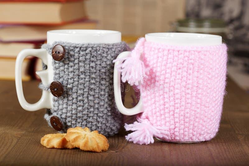 Para herbaciane filiżanki z trykotowymi pokrywami i ciastkami obrazy stock