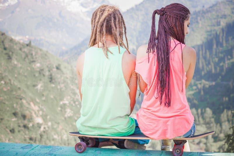 Para hipis, młodzi ludzie przy górą z longboard jeździć na deskorolce obraz stock
