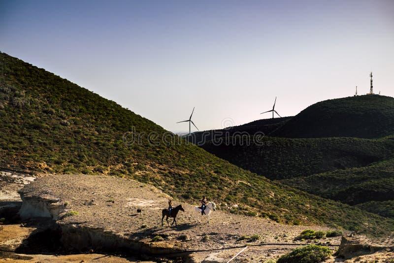 Para jeździec z koniami w przygoda czasu wolnego podróży aktywności w dolinie z górami i wiatrowymi młynami dla produkcji energii obrazy stock