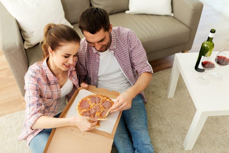 Para je takeaway pizzę w domu z czerwonym winem zdjęcie stock
