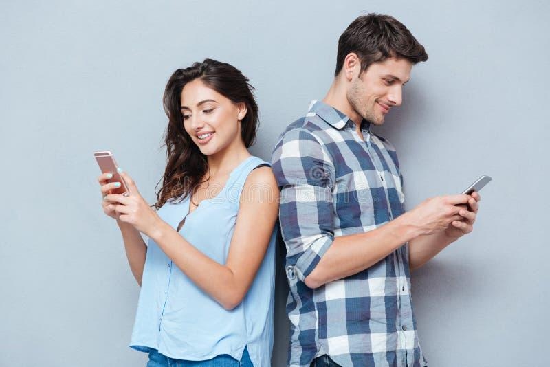 Para jest przyglądającym smartphone nad szarym tłem obrazy stock