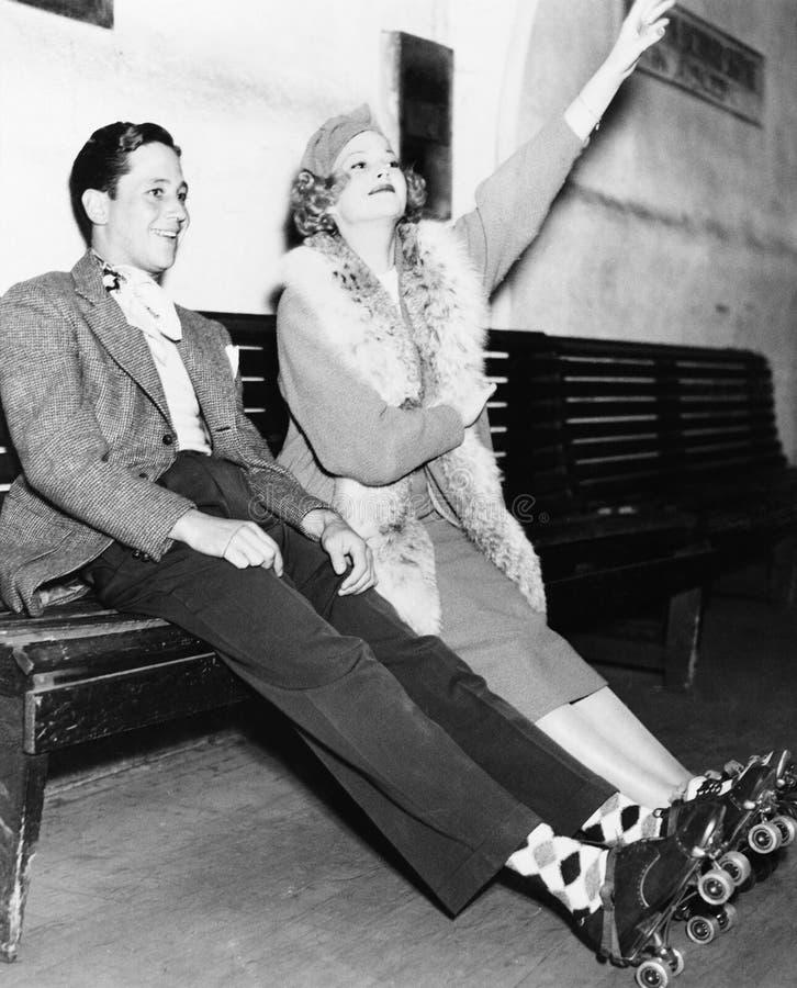 Para jest ubranym rolkowe łyżwy i obsiadanie na ławce (Wszystkie persons przedstawiający no są długiego utrzymania i żadny nieruc fotografia stock
