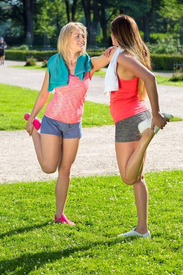 Para joggers rozciąga ich noga mięśnie zdjęcie royalty free