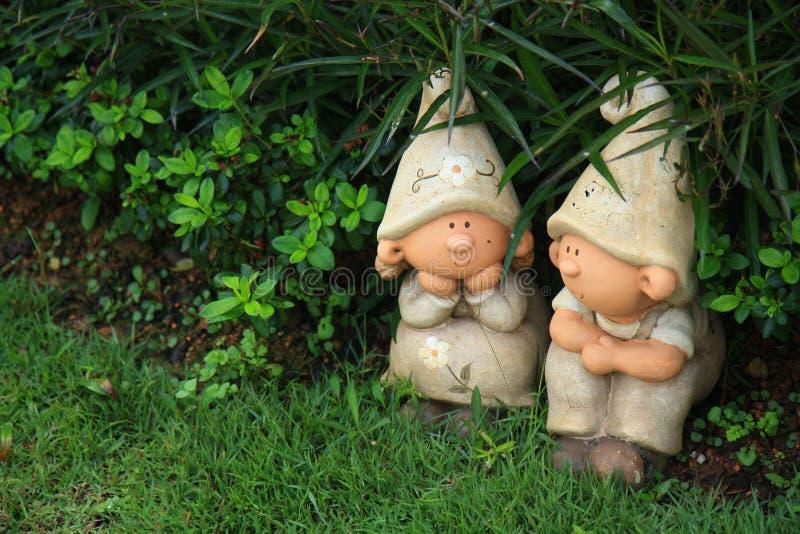 Para kamienny statuy obsiadanie za zielonym krzakiem w ogródzie obraz royalty free