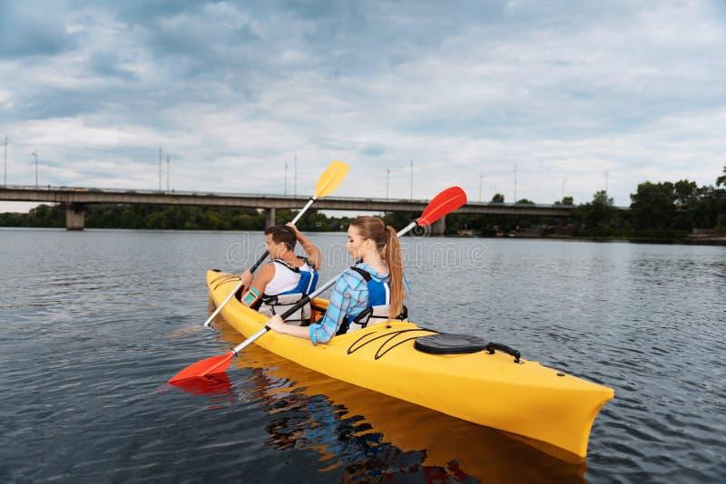 Para kayaking wpólnie sportowowie jest ubranym życie kamizelkę obraz stock