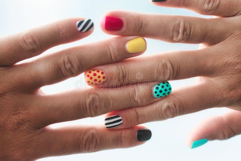 Para kobiet ręki z barwionymi malującymi gwoździami z różnymi wzorami obraz royalty free