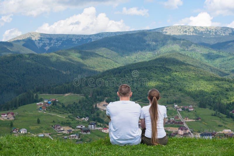 Para kochankowie siedzi na wzgórzu i podziwia widok góra fotografia royalty free