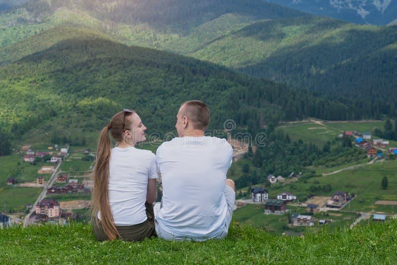 Para kochankowie siedzi na wzgórzu i podziwia widok góra obraz stock