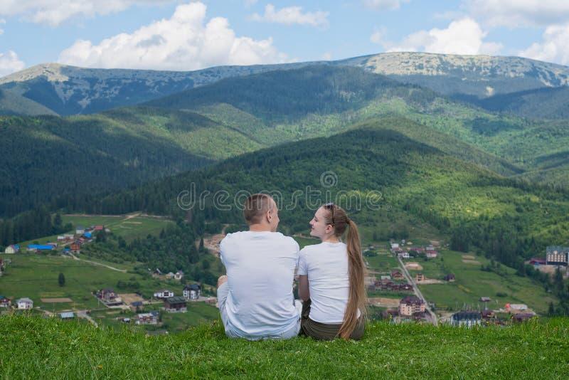 Para kochankowie siedzi na wzgórzu i podziwia widok góra zdjęcia royalty free