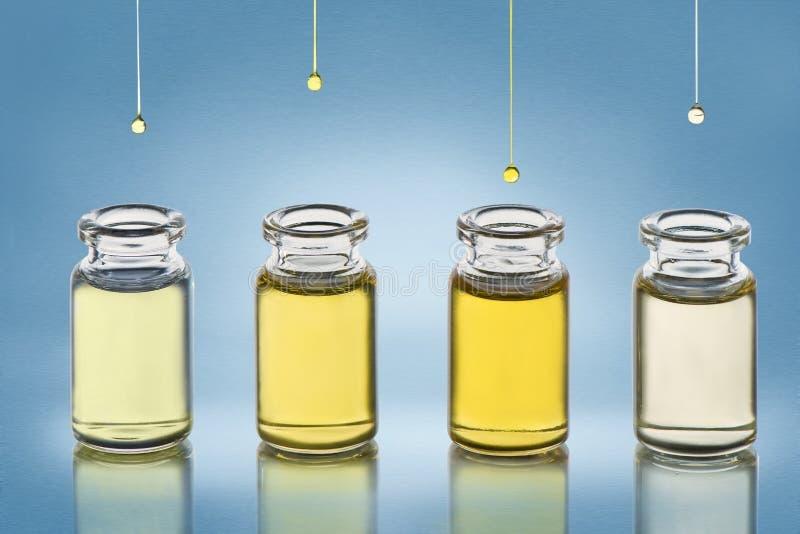 Para las botellas con diversos cosméticos engrase los soportes en el fondo metálico de la textura de la pendiente azul foto de archivo libre de regalías