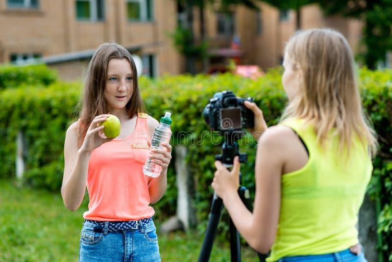 Para las colegialas de la muchacha, verano en naturaleza Registra un vídeo sobre la consumición sana En sus manos sostiene una ma fotografía de archivo