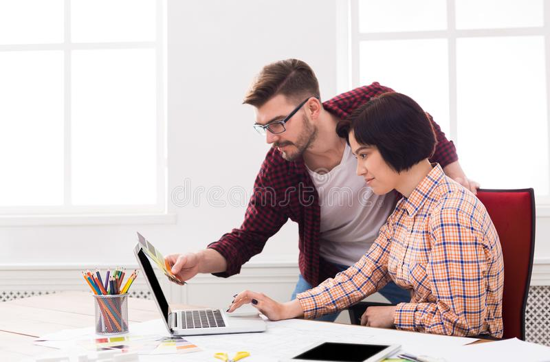 Para młodzi projektanci pracuje przy nowożytnym biurem obraz royalty free