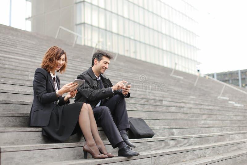 para małżeńska biznesowi nauczyciele używa pastylkę i smartphon fotografia royalty free