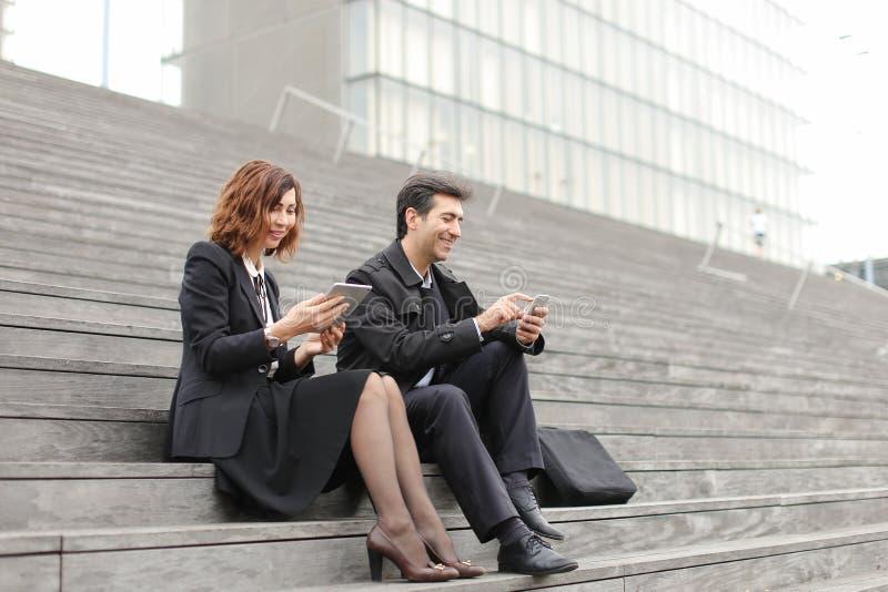 para małżeńska biznesowi nauczyciele używa pastylkę i smartphon zdjęcia stock