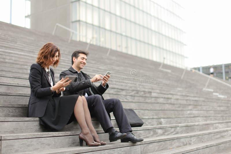 para małżeńska biznesowi nauczyciele używa pastylkę i smartphon obrazy stock