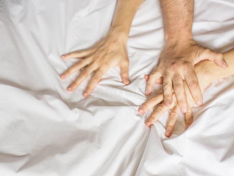 Para ma płeć Ręka trzyma mocno chwyty biały zmięty łóżkowy prześcieradło w pokoju hotelowym, znak ekstaza, czuć fotografia stock