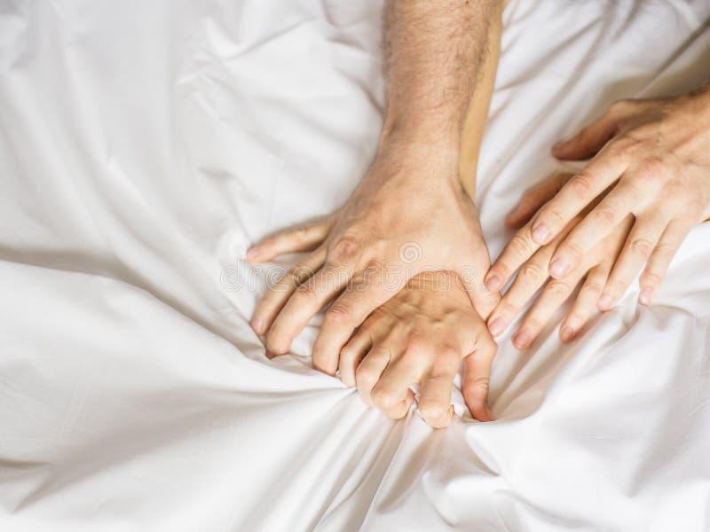 Para ma płeć Ręka trzyma mocno chwyty biały zmięty łóżkowy prześcieradło w pokoju hotelowym, znak ekstaza, czuć obrazy royalty free