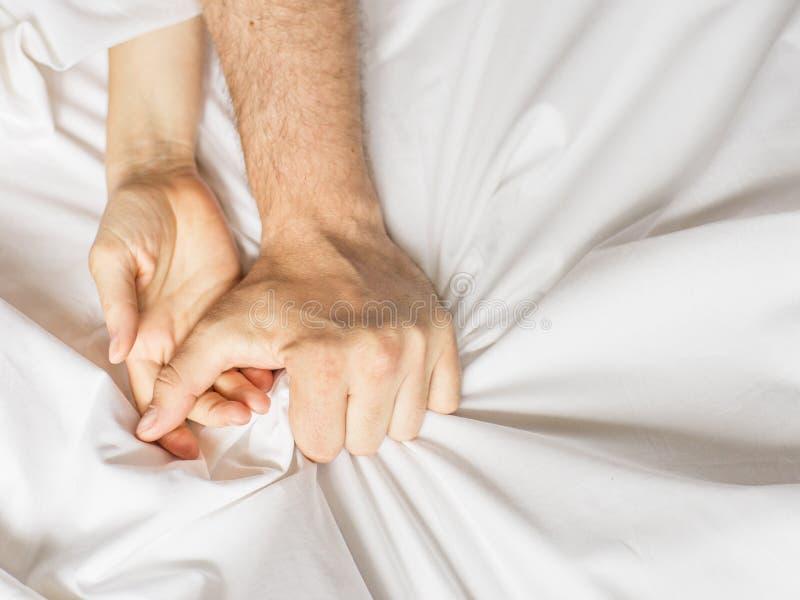 Para ma płeć Ręka trzyma mocno chwyty biały zmięty łóżkowy prześcieradło w pokoju hotelowym, znak ekstaza, czuć zdjęcia stock
