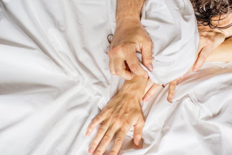 Para ma płeć Ręka trzyma mocno chwyty biały zmięty łóżkowy prześcieradło w pokoju hotelowym, znak ekstaza, czuć obraz stock