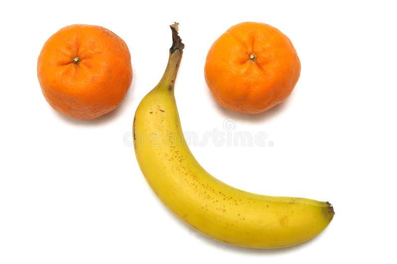 Para mandarynek pomarańcze i pojedynczy banan układał w formie twarzy zdjęcia stock