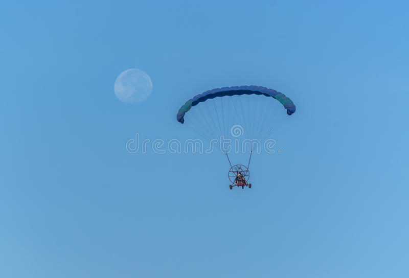 Para motor glider flying towards the moon stock images