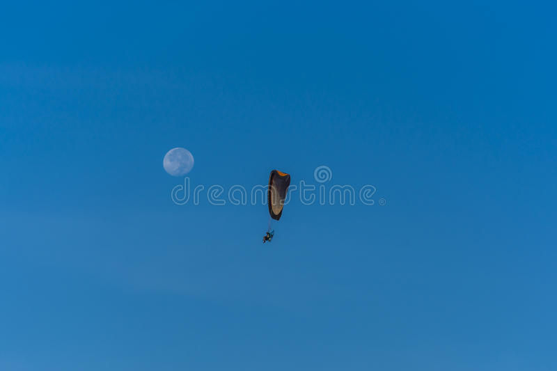Para motor glider flying towards the moon royalty free stock images