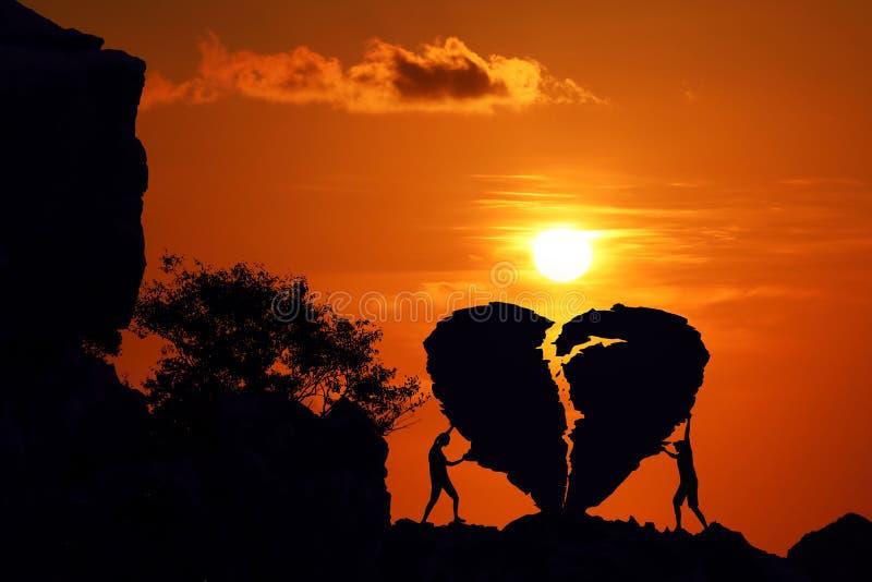 Para na złamane serce kształta skale na górze z czerwonym niebo zmierzchem obrazy royalty free