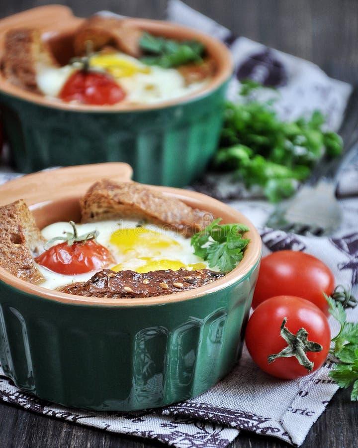Para o café da manhã, o ovo com pão e a cereja inteira dos tomates cozeram em moldes do forno imagem de stock royalty free