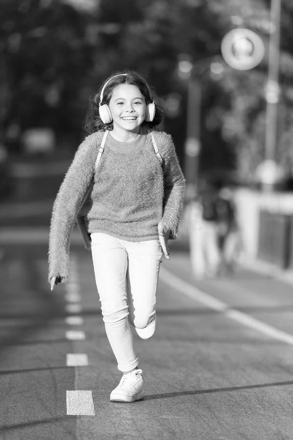 Para o dia feliz Menina bonito com fones de ouvido Pouca crian?a para apreciar a atividade Corredor de passeio da crian?a na m?si fotos de stock