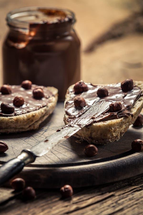 Para o sanduíche do pequeno almoço com nutella e porcas imagem de stock royalty free