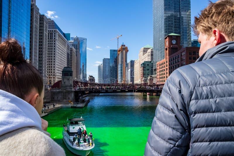 Para obserwuje partyjną łódź gdy ono krzyżuje farbującą zieloną Chicagowską rzekę obraz royalty free