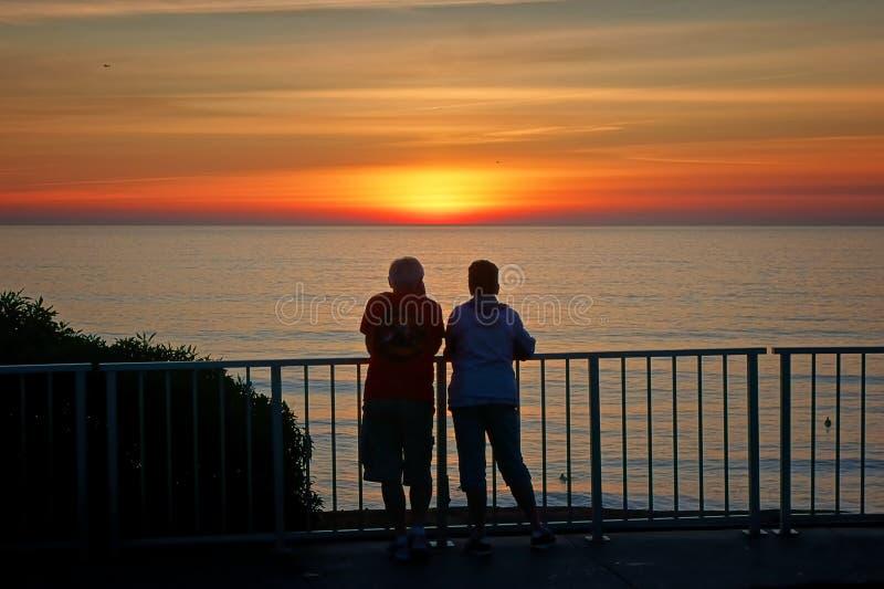 Para ogląda słońce set wiesza out przy poręczem fotografia stock