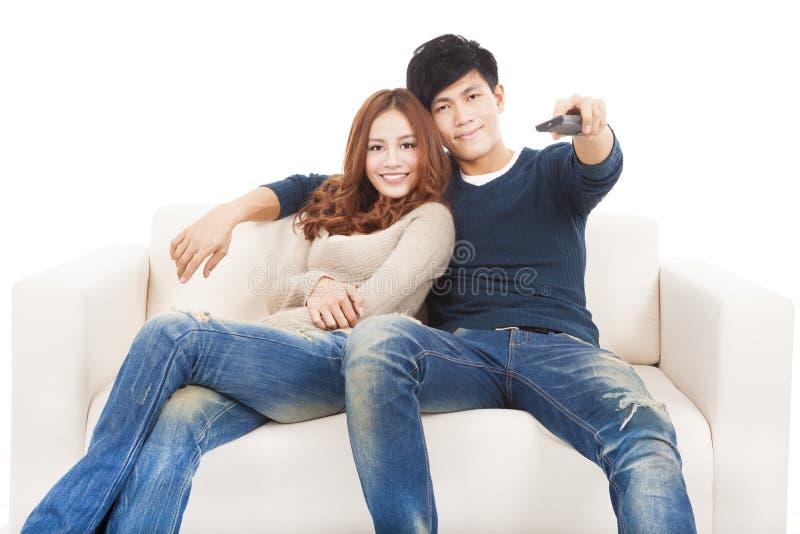 Para ogląda TV z pilot do tv na kanapie obraz stock