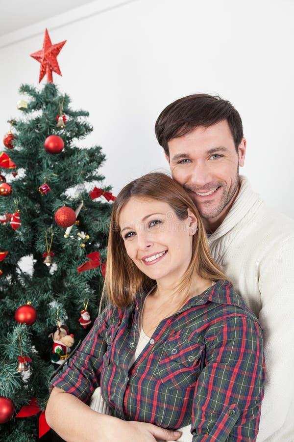 Para ono uśmiecha się obok chrismas drzewnych zdjęcia royalty free