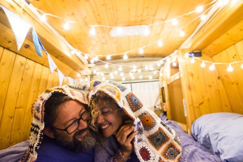Para osób zakochanych i związanych dobrze się bawi na wakacjach ze starym, odbudowanym vanem do małego domu - koncepcja życia van fotografia royalty free