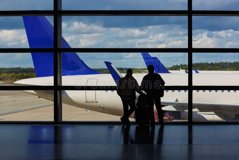 Para pasażery w lotnisku, patrzeje przez okno przy samolotami zdjęcie stock